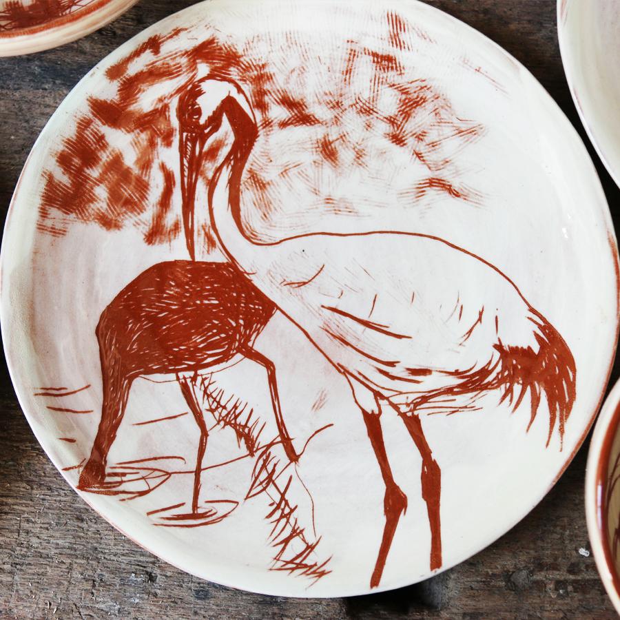 Assiette à décor de hérons réalisés au sgraphite à travers un engobe blanc recouvrant un engobe rouge.