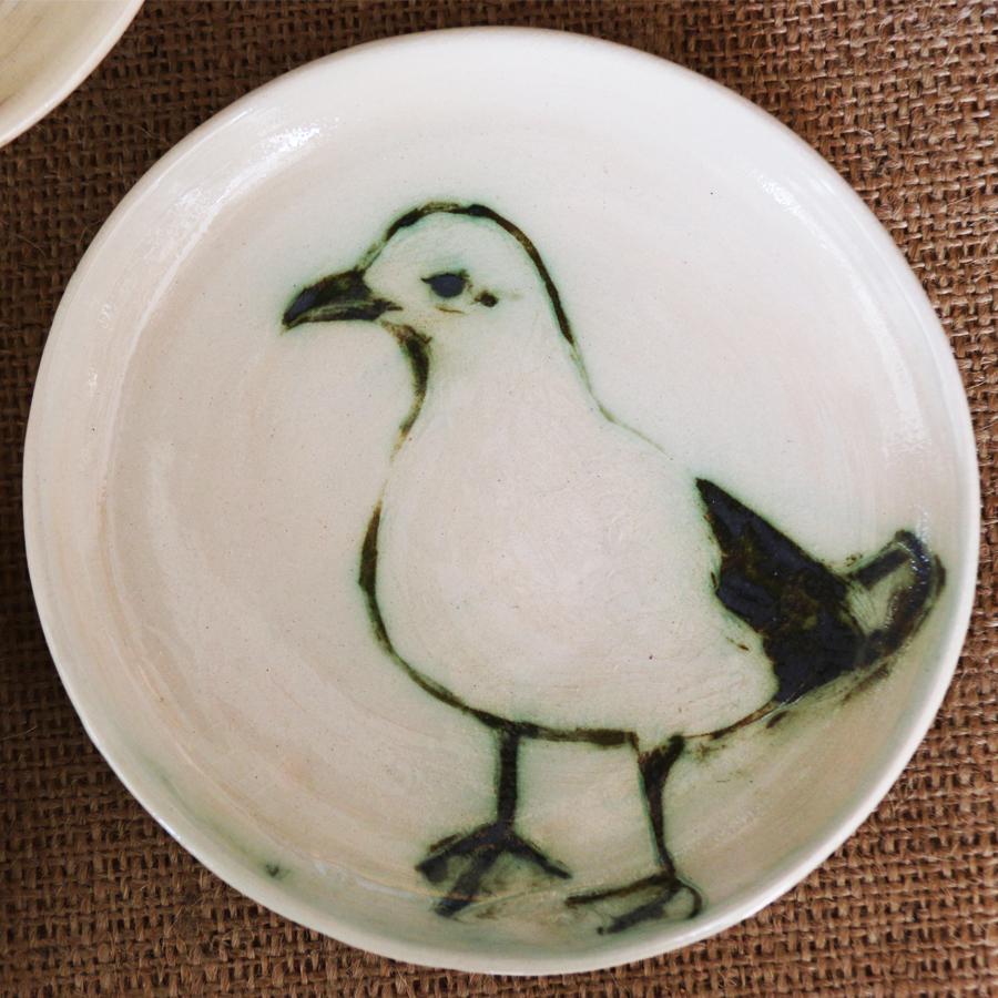 Assiette ornée d'un dessin de mouette à l'oxyde de cuivre sur fond à l'engobe blanc.