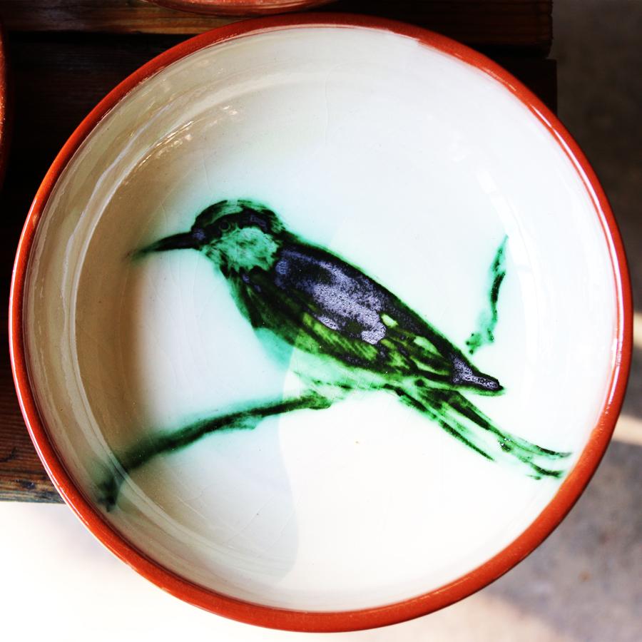 Assiette engobée en blanc, ornée d'une représentation de guêpier à l'oxyde de cuivre cernée d'un filet rouge.