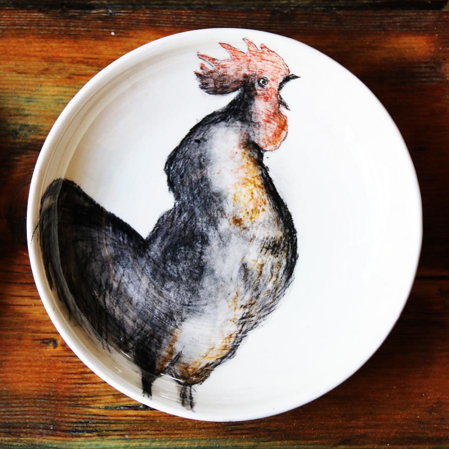 Assiette illustrée d'un coq réalisé aux craies d'oxydes sur fond blanc à l'engobe.