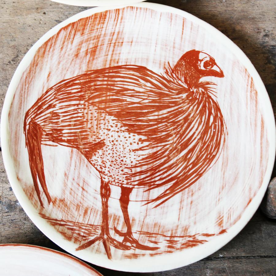 Assiette à décor de pintade réalisé au sgraphite à travers un engobe blanc recouvrant un engobe rouge