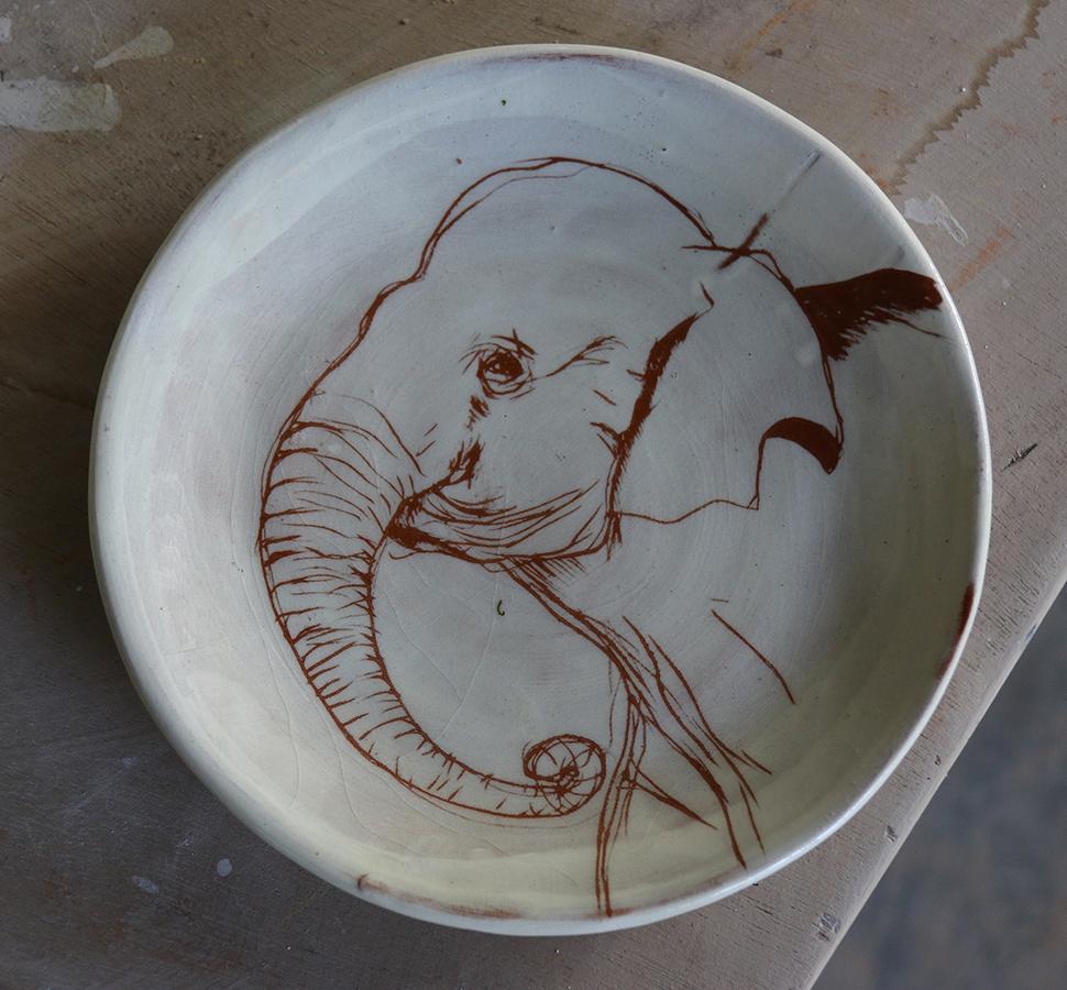 Assiette à décor d'éléphant réalisé au sgraphite à travers un engobe blanc recouvrant un engobe rouge.