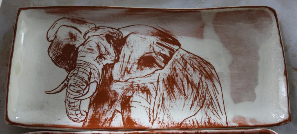 Plat à décor d'éléphant réalisé au sgraphite à travers un engobe blanc recouvrant un engobe rouge.