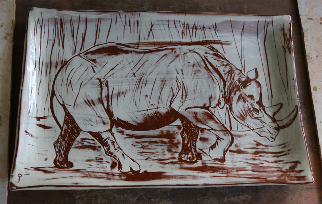 Plat à décor de rhinoceros réalisé au sgraphite à travers un engobe blanc recouvrant un engobe rouge.