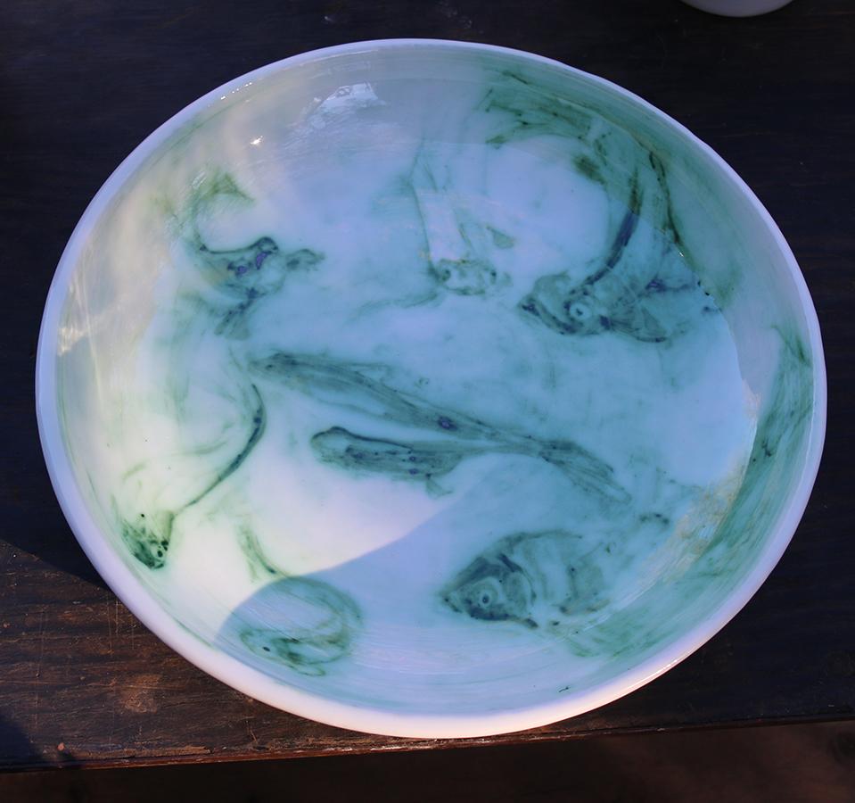 Saladier blanc à l'engobe et décoré de poissons à l'oxyde de cuivre.