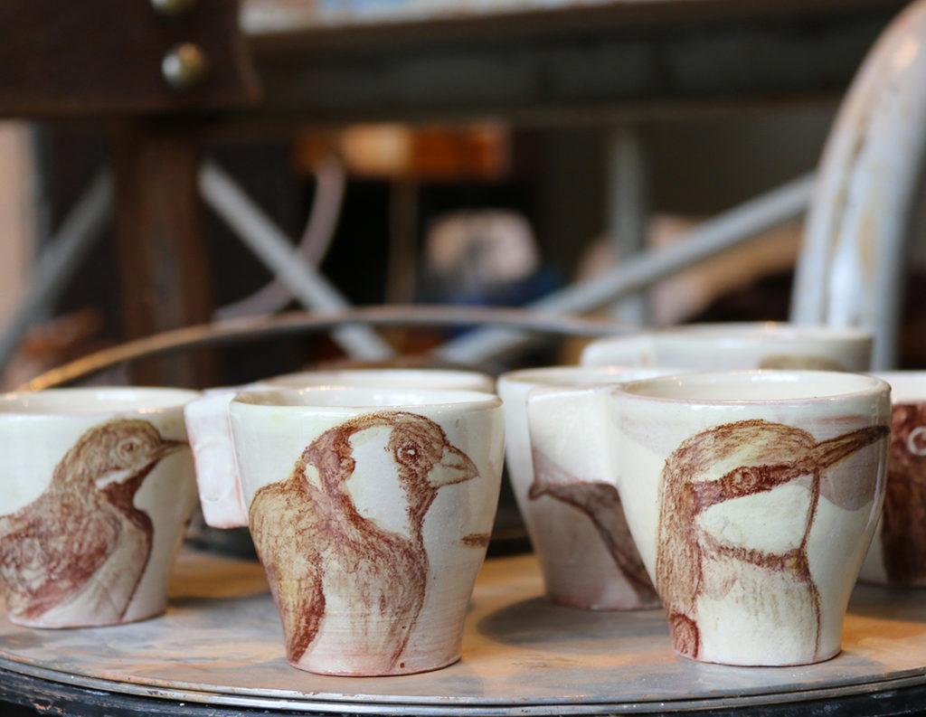 Tasses à café illustrées d'oiseaux réalisés aux craies d'oxydes sur fond blanc à l'engobe.