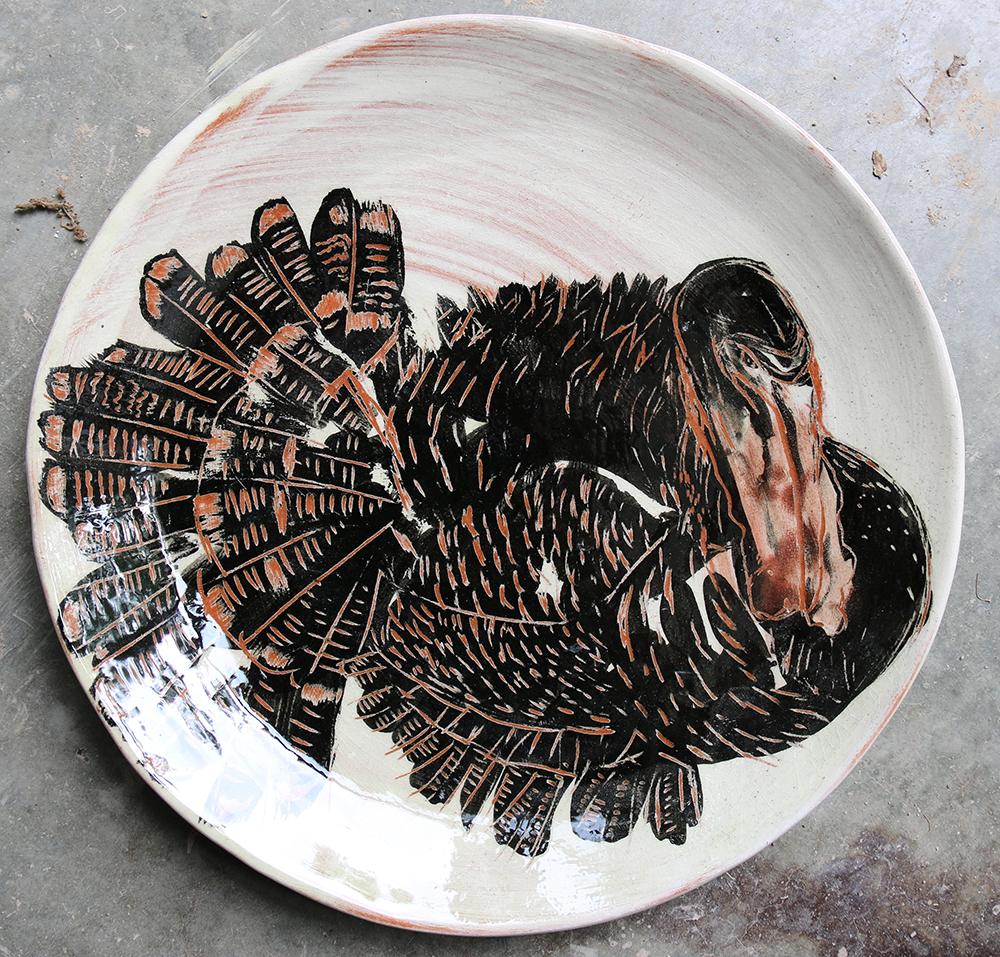 Assiette décorée d'un dindon réalisé selon la technique du sgraphite.