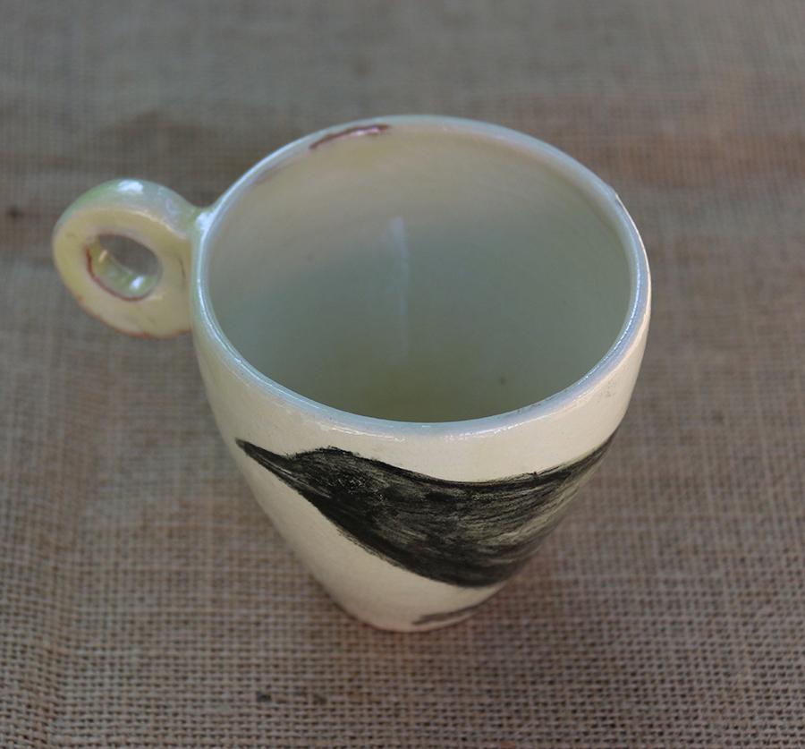 Tasse illustrée d'une Corneille réalisée aux craies d'oxydes sur fond blanc à l'engobe. Vue de dessus.