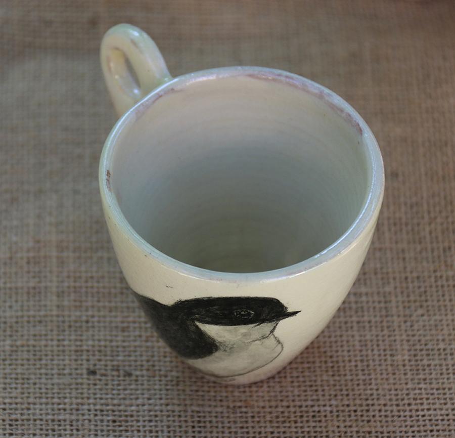 Tasse illustrée d'une Hirondelle des fenêtres réalisée aux craies d'oxydes sur fond blanc à l'engobe. Vue de dessus.