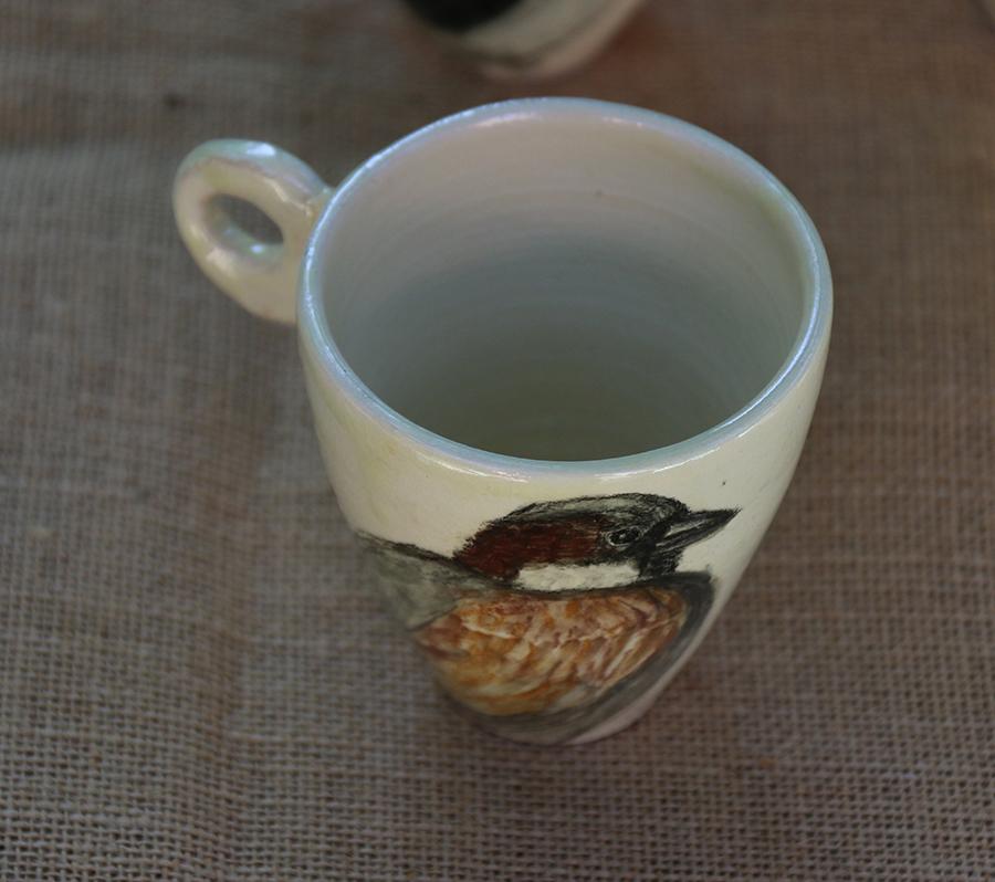 Tasse illustrée d'un Moineau domestique réalisé aux craies d'oxydes sur fond blanc à l'engobe. Vue de dessus.