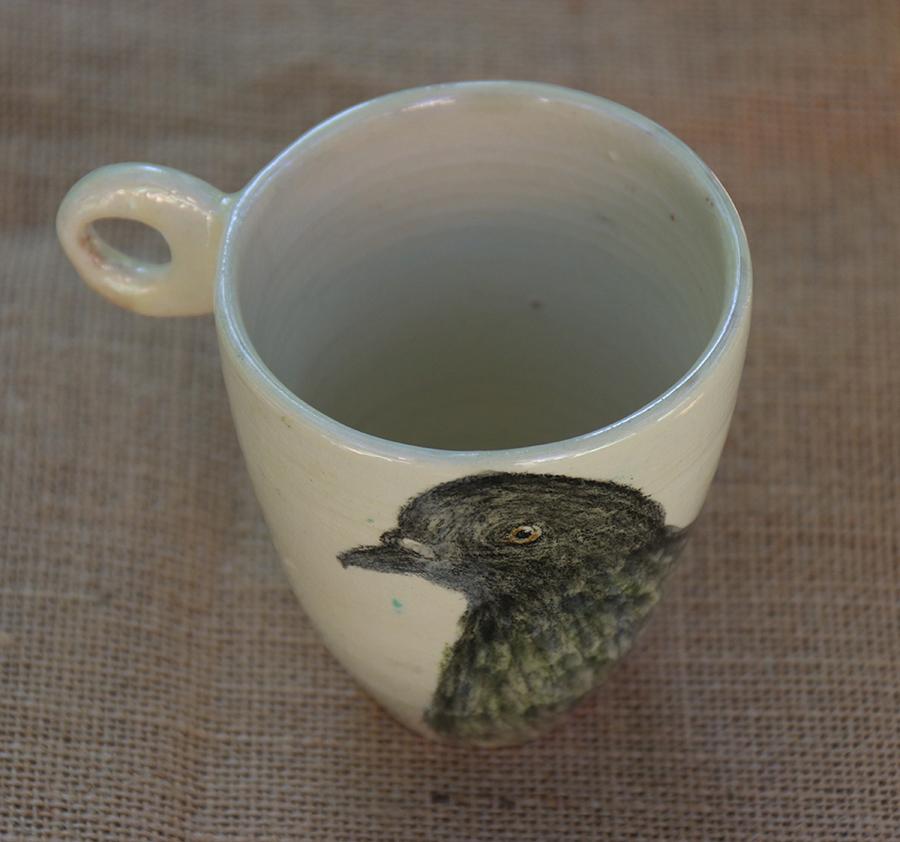 Tasse illustrée d'un Pigeon réalisé aux craies d'oxydes sur fond blanc à l'engobe. Vue de dessus.