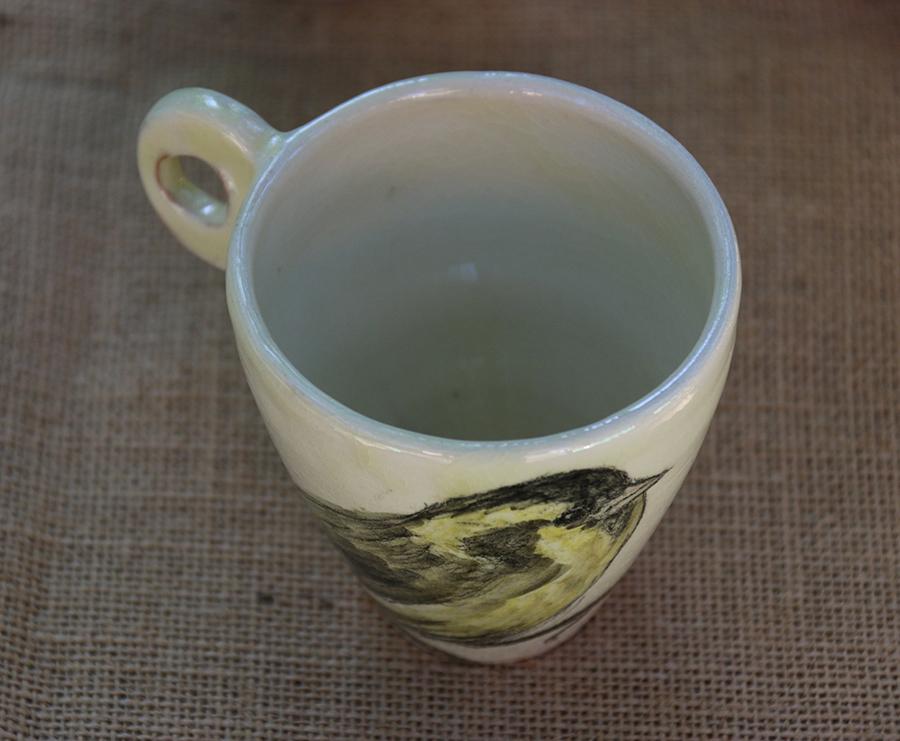 Tasse illustrée d'un Tarin des aulnes réalisé aux craies d'oxydes sur fond blanc à l'engobe. Vue de dessus.